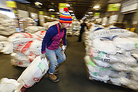 Kalyn MacDonald and a crew of volunteers, including a group from the Alaska Military Youth Academy, move, weigh and stack thousands of musher food drop bags that are headed to the 22 checkpoints along the trail at the Airland Transport facility in Anchorage, Alaska on Wednesday, February 17, 2016 just prior to Iditarod 2016
