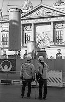 Berlino, viale Unter den Linden, quartiere Mitte. Due operai, di cui uno infortunato, osservano i lavori per la metropolitana davanti al Zeughaus (armeria), oggi sede del Deutsches Historisches Museum (Museo Storico Tedesco), in prossimità del Berliner Schloss (Castello di Berlino, in fase di ricostruzione) --- Berlin, Unter den Linden avenue, Mitte district. Two workers, one injured, observing the works for the underground in front of the Zeughaus (armoury), site of the German Historical Museum, near the Berliner Stadtschloss (Berlin Palace, under reconstruction)