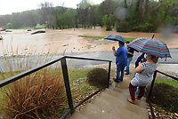 Jill Hall (right) and other workers at UL Verification Services look Wednesday April 28 2021 at flooding, including partially submerged vehicles, along Dream Valley Road on the east edge of Rogers. Go to nwaonline.com/210429Daily/ to see more photos.<br />