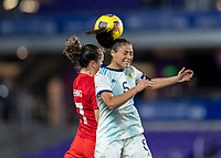 ORLANDO, FL - FEBRUARY 21: Jessie Fleming #17 of Canada goes up for a ball with Vanesa Santana #5 of Argentina during a game between Canada and Argentina at Exploria Stadium on February 21, 2021 in Orlando, Florida.