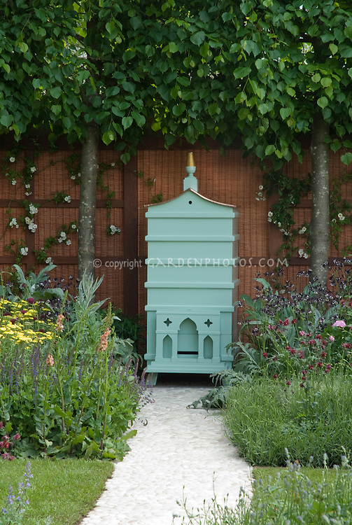 Beekeeping in flower garden, pretty beehive with many types of flowering plants