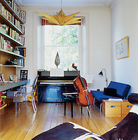 A home office come music and study room. The parchment star light is by designer Tom Dixon. The shelving is oak with an aluminium strip concealing lighting. The flooring is an oak plank floor with a bevelled edge.