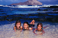 Kids playing in tidepool at Makapuu Beach Park, on Oahu's eastern coast. Rabbit island is in the background.