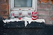 Empty Smirnoff bottles left by street drinkers on a window ledge in north London.