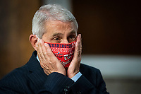 Anthony Fauci, director of the National Institute of Allergy and Infectious Diseases, adjusts a Washington Nationals protective mask while arriving to a Senate Health, Education, Labor and Pensions Committee hearing in Washington, D.C., U.S., on Tuesday, June 30, 2020. Top federal health officials are expected to discuss efforts to get back to work and school during the coronavirus pandemic. <br /> Credit: Al Drago/CNP/AdMedia