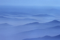 Misty white morning clouds with mountain ridges