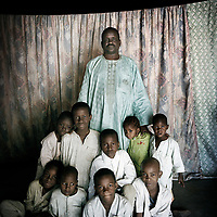 Al Haj Boukar, 46, with eight of his sons and daughter in Maroua. <br /> <br /> Boukar was a wealthy business owner who fled the conflict and is now plunged into poverty with his family of eleven, including his mother Hadjia, who is estimated to be about 100 years-old. He lives behind a rusty metal gate in a small compound with two small buildings that house his two wives and 14 children, several of whom are his brother's and were orphaned in the attack on their village. The children are aged from 2 months to 18 years old. There are only four small rooms for everyone to sleep in and the rent costs 55,000 CFA a month (around GBP70). <br /> <br /> 'I look after fourteen children, two wives and my mother. Four are orphans, the children of my brother who was shot when armed men entered my village. They entered on a Wednesday at 4.00pm. They spent the night in the town and left the following day. I was a target. They were looking for me in person. They come for wealthy people. They say 'give us money and we'll do God's work'. If we refuse, they kill you. I had to flee and leave my family. They even searched for me in the ceiling. They took off the ceiling to make sure I wasn't hiding there.<br /> <br /> 'My daughter, who was with my brother, was also shot. We brought her to the hospital here in Maroua to get treatment. I was very very scared that since they killed my brother and shot my daughter, if they got me they would have killed me as well. My daughter was just collateral damage. She wasn't a target. But since they were together, she was shot. She is 13 and she is OK. She lives here with us. <br /> <br /> 'When I left I came to Maroua and then my family also fled to Mora. I sent a car to go and get them there. I was very afraid because I knew my brother was already killed. <br />  <br /> 'I knew people here in town. So I asked people to help me find a place to rent. I found this place. I know the man who owns it. In my village there is not even a single fly that is left there. I would not leave Maroua.<br /> <br /> 'In my village I had