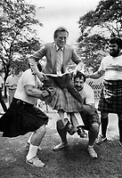 A fellow could get kilt! This event in preparation for the Fergus Highland games tomorrow is called tossing in the mayor and is performed by two heavyweights whose usual caper is tossing a caber. Giving Toronto's Art Eggleton a tumble in Nathan Phillips Square are Keith Tice; left; and Dave Harrington; as Dan Markovic looks on.