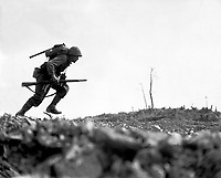 A Marine dashes through Japanese machine gun fire while crossing a draw, called Death Valley by the men fighting there.  Marines sustained more than 125 casualties in eight hours crossing this valley.  Okinawa, May 10, 1945.  Pvt. Bob Bailey.  (Marine Corps)<br /> NARA FILE #:  127-N-120562<br /> WAR & CONFLICT BOOK #:  1229