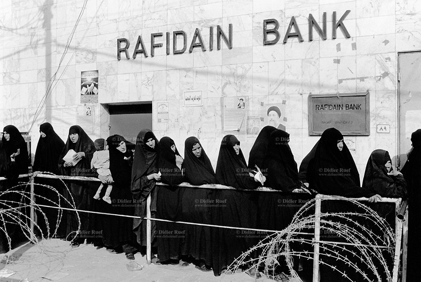 Iraq. Najaf. Iraqi women, all widows who lost their husbands in the wars, wait on line at the entrance of the Rafidain bank to get their monthly pensions. The women wear the abaya and the hijab (islamic headscarf) on their heads to cover their hair. The abaya, sometimes also called aba, is a simple, loose over-garment, essentially a robe-like dress, worn by some women in parts of the Islamic world. Traditional abaya are black and may be either a large square of fabric draped from the shoulders or head or a long caftan. The abaya covers the whole body except the face, feet, and hands. The word hijab (or hidjab) refers to both the veil covering the head and traditionally worn by muslim women (Islamic headscarf), but also the  modest muslim styles of dress in general. 26.02.04 © 2004 Didier Ruef .