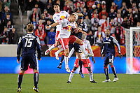 Juan Pablo Angel (9) and Joel Lindpere (20) of the New York Red Bulls go up for a header with Pat Phelan (28) of the New England Revolution. The New York Red Bulls defeated the New England Revolution 2-0 during a Major League Soccer (MLS) match at Red Bull Arena in Harrison, NJ, on October 21, 2010.