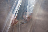 A boy looks outside from his tent. outskirts of Kathmandu, Nepal. May 11, 2015