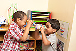 Education preschool 3-4 year olds two boys laughing and looking at each other through binoculors made from tape and carboard tubes horizontal