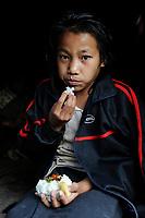 LAOS province Oudomxay , village Houyta, ethnic group Khmu, girl eats sticky rice / LAOS Provinz Oudomxay Dorf Houyta , Ethnie Khmu , Maedchen isst Klebreis