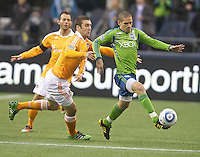 Seattle Sounders FC midfielder Osvaldo Alonso , right, dribbles the ball in front of Houston Dynamo forward Will Bruin during play  at Qwest Field in Seattle Friday March 25, 2011. The match ended in a 1-1 draw.