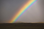 Brilliant rainbow over open country in western Montana