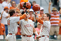 Texas Longhorns teammates Ben Johnson (14), Tres Barrera (1)  greet Mark Payton (2) at home after his 2 run home run in the first inning of the NCAA baseball game against the Houston Cougars on June 6, 2014 at UFCU Disch–Falk Field in Austin, Texas. The Longhorns defeated the Cougars 4-2 in Game 1 of the NCAA Super Regional. (Andrew Woolley/Four Seam Images)
