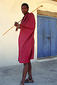 Makoni, Tanzania. Masai tribesman wearing traditional red cloth and holding stick outside a house with a blue door.