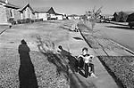 Dallas, Texas development with kids riding big wheels on sidewalk. 1975