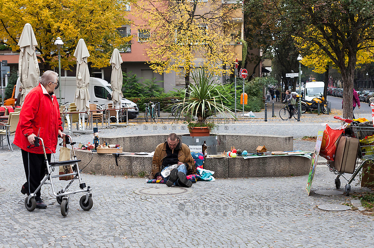Berlino, quartiere Kreuzberg. Un venditore ambulante dall'aspetto semicosciente e una anziana signora con deambulatore --- Berlin, Kreuzberg district. A street seller looking half-conscious and an old lady with walker