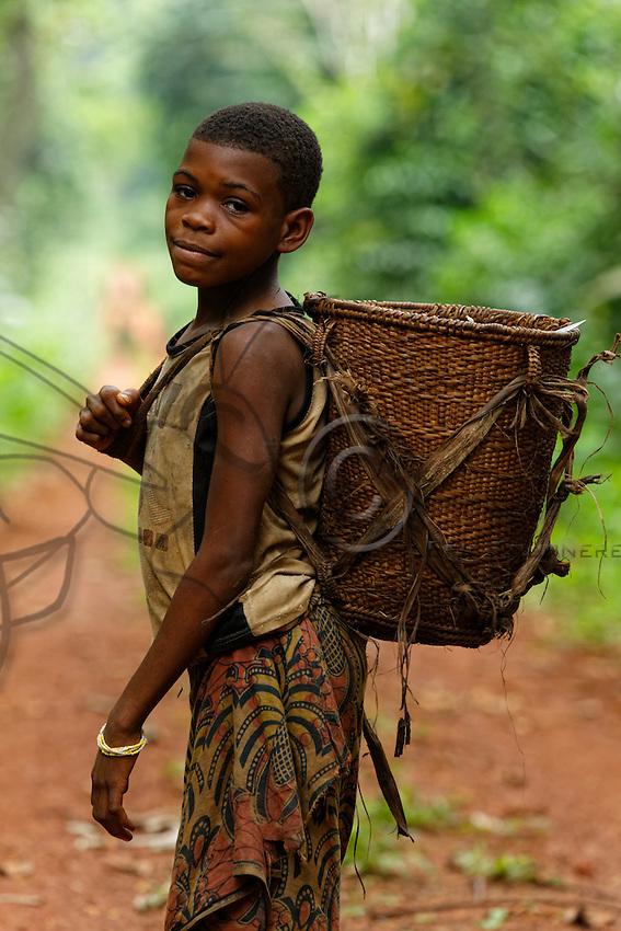 """A young girl with her basket, the """"Ykoua"""", on the forest track that leads to the town.///Une jeune fille avec son panier, le «Ykoua» sur la piste forestière qui mène à la ville."""