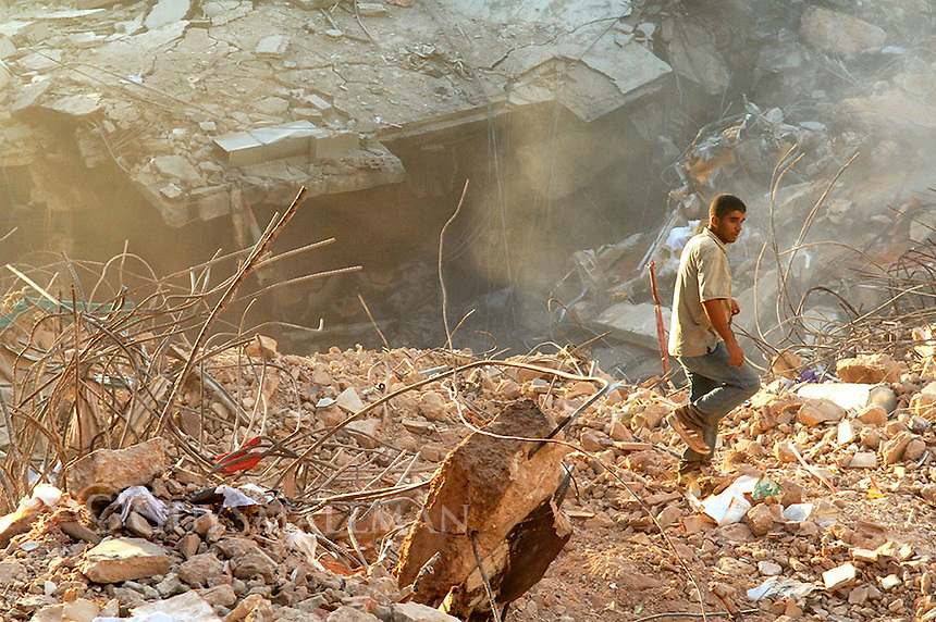 Man walks past destroyed residential block at sunset.