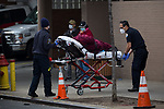 Healthcare workers wheel a patient to the emergency room during the coronavirus pandemic (COVID-19) in front of Wyckoff Heights Medical Center in the Brooklyn borough of New York City on April 5, 2020.  Photograph by Michael Nagle