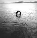 Vintage black and white. Brendan Works in inner tube searching. Moosehead Lake, ME. 1997,  97-082-012 negative file #.