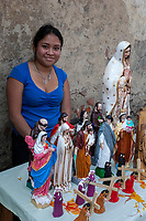 Antigua, Guatemala.  Young Lady Selling Religious Figurines.