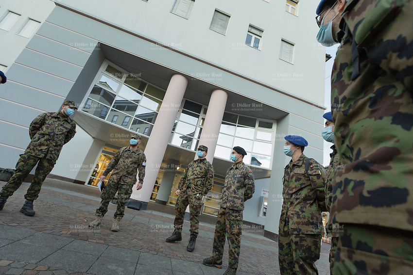 """Switzerland. Canton Ticino. Locarno. Ospedale Regionale di Locarno La Carità. Due to the spread of the coronavirus (also called Covid-19), the Federal Council has categorised the situation in the country as """"extraordinary"""". The army was called upon to provide its troops in terms of medical assistance. The militia soldiers from medical troops were called by the Swiss army for the first time since World War II. Under the country's militia system, professional soldiers constitute a small part of the military and the rest are conscripts or volunteers aged 19 to 34 (in some cases up to 50).  All men and a woman, dressed with camouflage uniforms, stand outside the main entrance to the hospital. They all were a mask to protect themselves from the coronavirus ( also called Covid-19). 20.11.2020 © 2020 Didier Ruef"""
