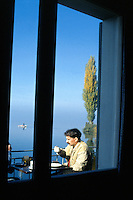Switzerland. Zoug. Autumn season. A man is seated in a restaurant and drinks  coffee. A fisherman is on his boat on the lake of Zoug . © 1989 Didier Ruef