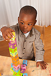 2 year old toddler boy building block tower with alphabet blocks