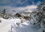 Greenleaf Hut with Mount Lafayette in the background in the White Mountain National Forest, New Hampshire covered in snow. This hut is closed during the winter season.