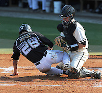 Catcher David Roney (8) of the Wofford College Terriers tags out Tyler Zupcic (28) of the Appalachian State Mountaineers at the plate in a game on April 28, 2012, at Russell C. King Field in Spartanburg, South Carolina. (Tom Priddy/Four Seam Images)