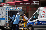 Healthcare workers wheel a patient to the emergency room during the conronavirus pandemic (COVID-19) at the  Wyckoff Heights Medical Center in the Brooklyn borough of New York City on April 5, 2020.  Photograph by Michael Nagle