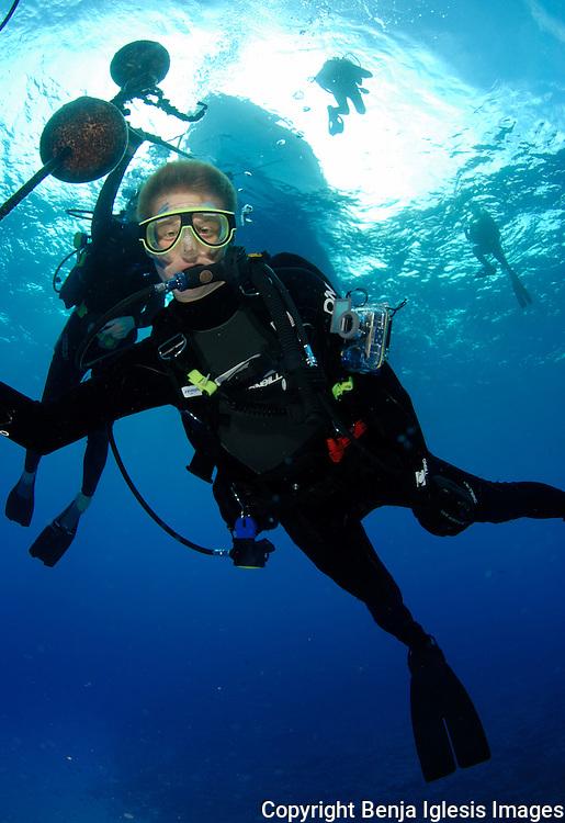 Diver with poseidon regulator doing safety stop at reefs end Molokini Maui Hawaii.