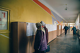 Voters read the programs of the presidential candidates, which hang on the walls of the gymnasium 4, one of the polling stations in Lutsk.