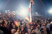 Berlin, Germany<br /> October 3, 1990<br /> <br /> In front of the Reichstag, the two Germany's -East and West - were reunited the second a massive German flag reached the top of the flag pole.<br /> <br /> Large crowds gathered for the event, nearly one year after the Berlin Wall was opened allowing East Germans to travel freely to the West. By October 1990 almost nothing remained of the wall.