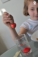 Girl (7-8) washing cherries in a glass of water at lunch in the kitchen (Licence this image exclusively with Getty: http://www.gettyimages.com/detail/81867390 )
