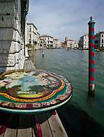 A colourful 'pali da casada' stands sentry to the terrace of Lars Rachen's Venetian apartment. His prized Fornasetti-topped dining table brought out into the light so its glory can be appreciated