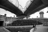 Milano, quartiere Moncucco - Famagosta, periferia sud. Un ragazzo e una ragazza nella piazzetta sotto al cavalcavia autostradale di piazza Maggi --- Milan, Moncucco - Famagosta district, south perifery. A boy and a girl under Maggi square's highway overpass