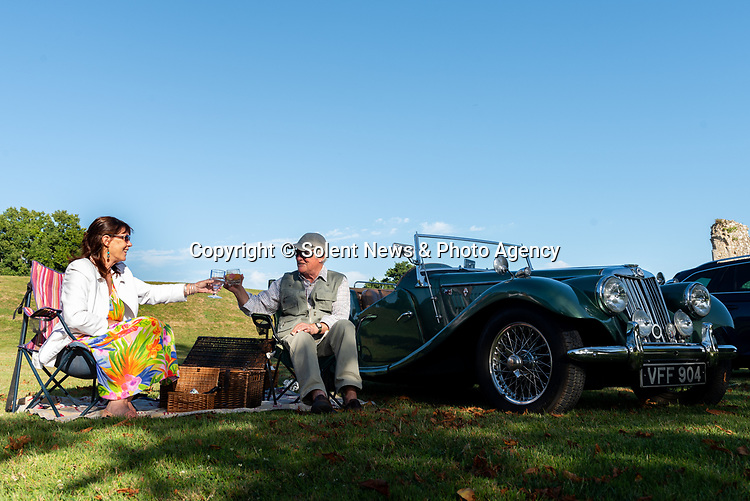 Pictured: Ann Marie Webley and Chris Richards toast a drink next to their 1954 MG TF 1500 during the Park & Picnic event at National Motor Museum, Beaulieu in the New Forest, Hants.<br /> <br /> The Park and Picnic event, allows motorists to park in bays designated for social distancing regulations and enjoy an evening of music and entertainment on the grounds of the National Motor Museum, Beaulieu.<br /> <br /> © Jordan Pettitt/Solent News & Photo Agency<br /> UK +44 (0) 2380 458800