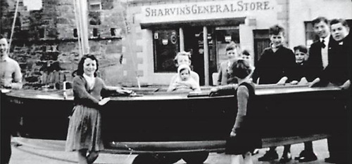 It's 1959, and the completion of Wychcraft sailing dinghy no 14 has to be marked with a celebratory stop outside Sharvin's, the beating heart of Strangford village.   Photo: Courtesy SSC