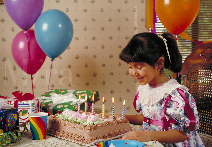 HISPANIC 6-YEAR-OLD GIRL BLOWS OUT THE CANDLES ON HER BIRTHDAY CAKE. HISPANIC 6 YEAR OLD GIRL. SAN FRANCISCO CALIFORNIA USA.