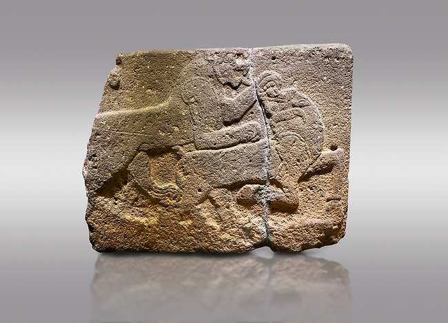 Picture & image of Hittite monumental relief sculpted orthostat stone panel of a Procession. Basalt, Karkamıs, (Kargamıs), Carchemish (Karkemish), 900-700 B.C. Anatolian Civilisations Museum, Ankara, Turkey. Two animals struggling with each other. The lion attacking the bull holds the bull's chin and turns it backwards.  <br /> <br /> Against a gray background.