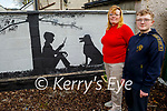 Martina and Jack Brosnan standing in their garden in Spa Road with their mural The Tree of Life that Martina painted for her son Jack.