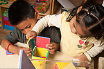 Education preschool 3-4 year olds boy and girl building together with magnetic blocks making home for small plastic bears