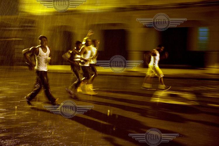 Boys run along a street in the rain as night falls on the island of Limones.