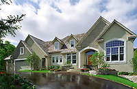 The front exterior of an executive style stone home with sweeping driveways and landscaping.