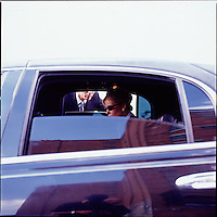 Man looking through limousine window at woman inside<br />